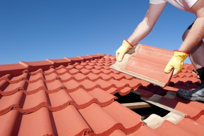 Man repairing tile roof